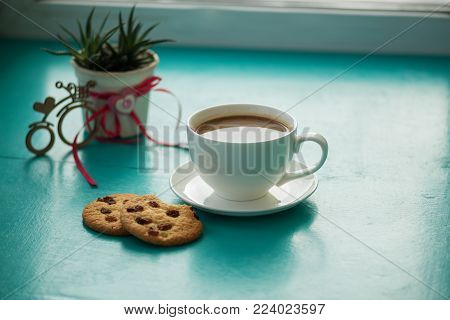 Valentine's Day, breakfast for your favorite - big cup of coffee with a cookies stands on a green surface, next to a cactus and a bicycle symbol with a heart. Top view.