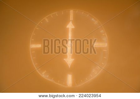 Blurred drown clock shows six o'clock. Golden blur background.