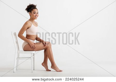 Full length portrait of satisfied girl bragging about her body shape while sitting on stool and smiling. Copy space in right side. Isolated on background