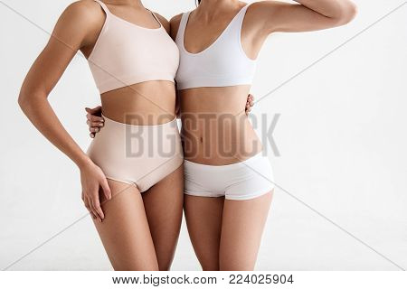 Thin women demonstrating their good looking figures in tight underwear. Isolated on background