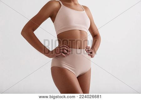 Fitness as a lifestyle. Close up of fit female body standing in comfortable lingerie. Isolated on background