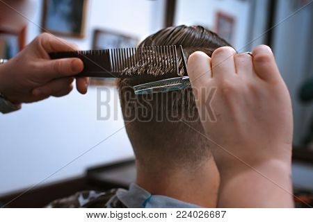 It's time for a new hairdo.The hands of the hairdresser hold a comb and scissors. haircut in the hairdresser's.Master hairdresser performs a man's haircut