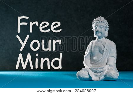 Free your mind - motivating text with white statuette of Buddha. Yoga and meditation concept.