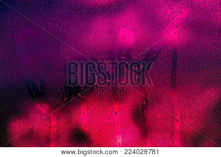 Love background, dark bright pink photo of a wet window with raindrops on it and handwriting word love, passion and desire concept, greeting card for Valentines day holiday