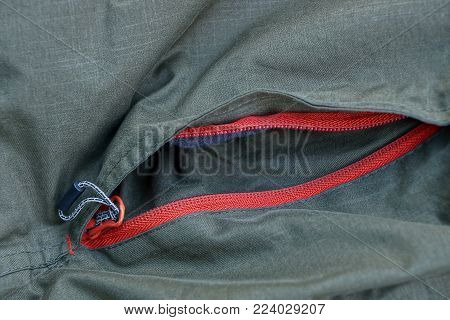 Green texture with a pocket and a red clasp