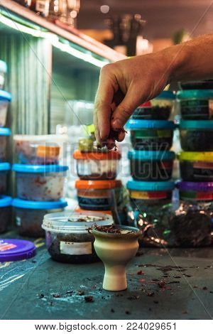 Shisha hookah preparing by barman. Bartender lays tobacco for smoking in hookah