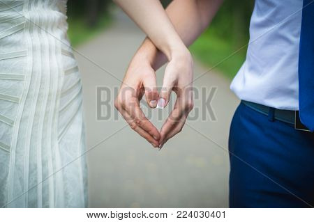 two newlyweds hold hands in the shape of a heart