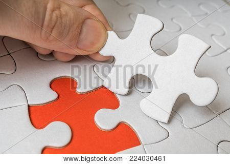 Hand Of A Man Is Connecting One Last Piece Of White Empty Puzzle