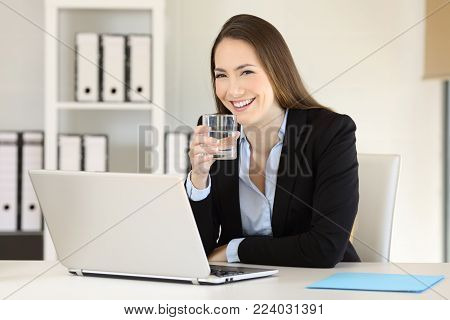 Happy executive holding a glass of water and looking at camera at office