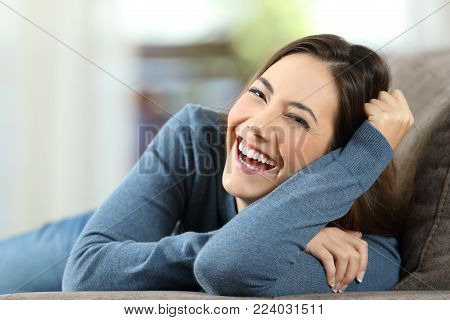 Portrait of a happy woman laughing with perfect teeth looking at camera sitting on a couch in the living room at home
