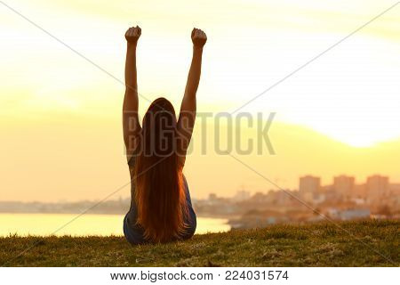 Back view backlight portrait of an excited single woman raising arms watching the sunset on the city with a warm light in the background