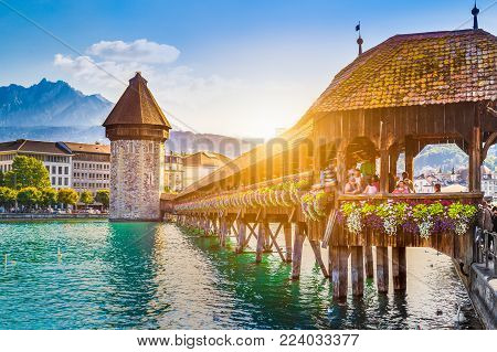 Historic city center of Lucerne with famous Chapel Bridge, the city's symbol and one of the Switzerland's main tourist attractions, and Mount Pilatus summit in the background in golden evening light at sunset, Canton of Lucerne, Switzerland