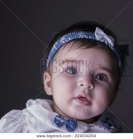 Close-up portrait of a 5 month old baby girl, directly looking through camera. Cute little baby girl