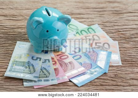 Financial savings money account or Europe economics concept, blue piggy bank on pile of Euro banknotes on wooden table, future growth of interest compound in saving or investing idea.