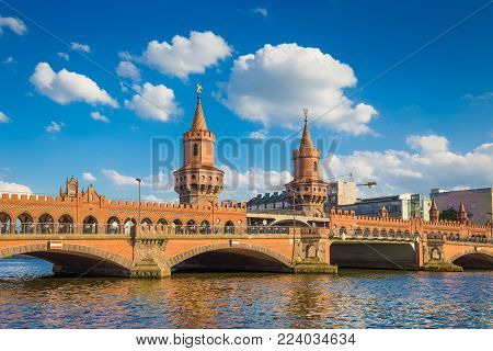 Beautiful view of famous Oberbaum Bridge crossing the Spree river on a sunny day with blue sky and clouds in summer, Berlin, Germany