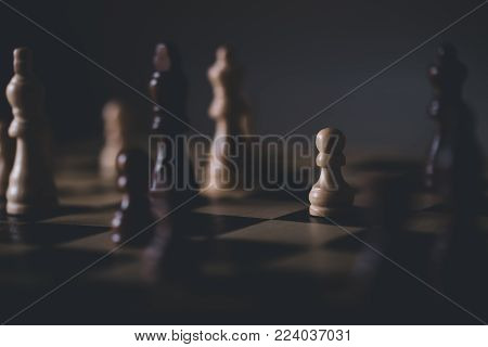 Wooden material chess board and chess pieces in low light with shallow depth of field