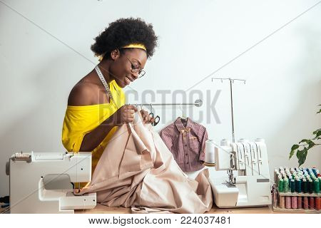 Young african woman seamstress looking at pink fabrics and standing in workshop