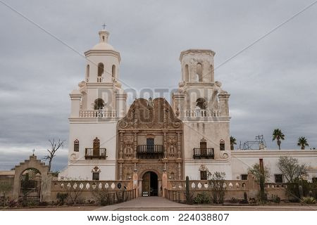 Tucson, Arizona, USA - January 9, 2018: Closeup of White and brown front facade of Historic San Xavier Del Bac Mission under heavy gray, white cloud deck. Some greenish desert plants in front.