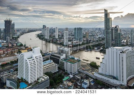 Bangkok city - construction of a two high-rise silhouette building with a crane on sunset sky background , cityscape bangkok Thailand