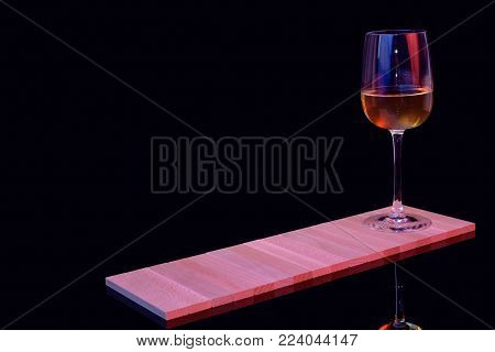 A glass of white wine on a black background on a wooden stand