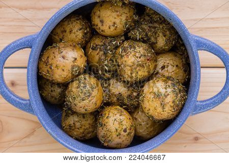 Overhead view of bowl of potatoes covering in seasoning on wood background.