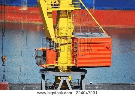 Bulk cargo ship under port crane bridge