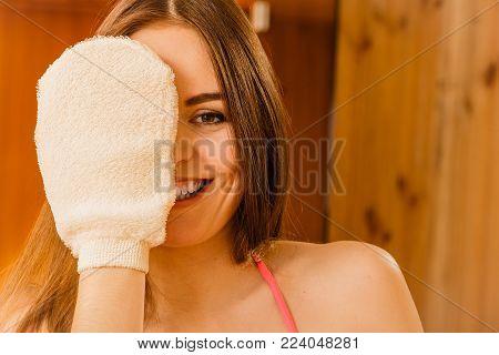 Funny young woman in wood finnish spa sauna with exfoliating glove. Girl in bikini relaxing. Skin care concept.