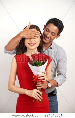 Handsome Asian man covering eyes of his smiling girlfriend with hand while passing her bouquet of red roses, isolated white background