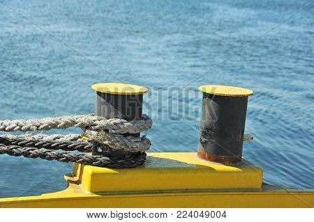 Old mooring bollard with rope in port