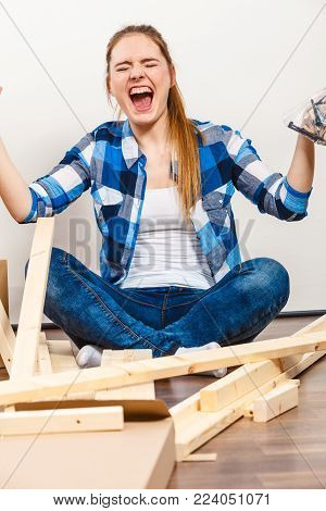 Stressed woman assembling wooden furniture. DIY enthusiast holding screws and parts. Young girl doing home improvement.