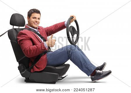 Elegantly dressed man seated in a car seat driving and making a thumb up sign isolated on white background