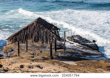 Thatched surfer shack atop rock formations at Windansea Beach in La Jolla, California.