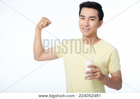 Waist-up portrait of handsome Asian man flexing his muscles while holding glass of milk in hand, isolated on white background