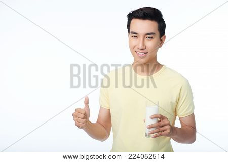 Confident young man with toothy smile showing thumb up and holding glass of milk in hand while standing against white background, waist-up portrait shot