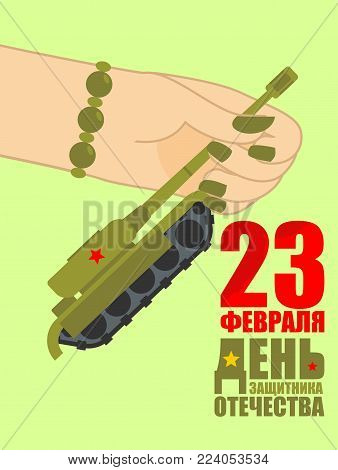 February 23. Woman hand giving tank toy. Traditional gift for men on Day of Defender of Fatherland in Russia. Translation text Russian. February 23.