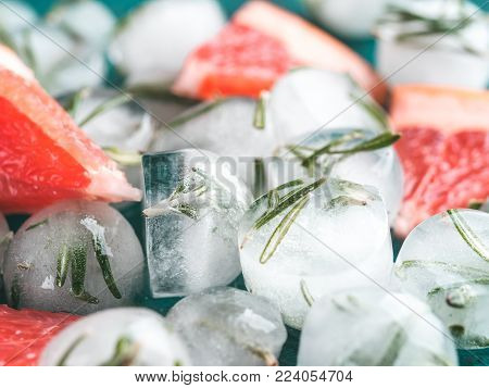 Close up view of detox rosemary ice cubes and fresh rosemary slice over green cement background.