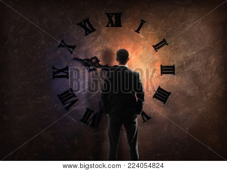 young businessman in black suit standing by wall with big clock with Roman dial, view from back