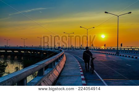 People relaxing on curved coastal road with street lamp and orange sky at sunset in Chonburi, Thailand.