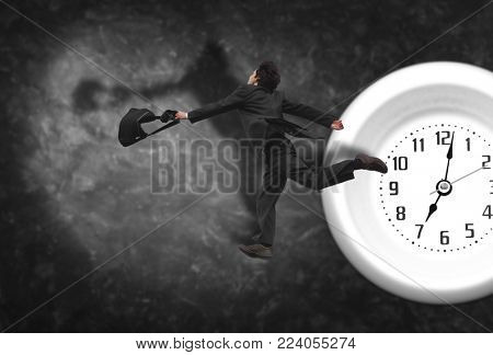elderly man tries to catch time, collage with running man in gray suit and clock on dark plaster background