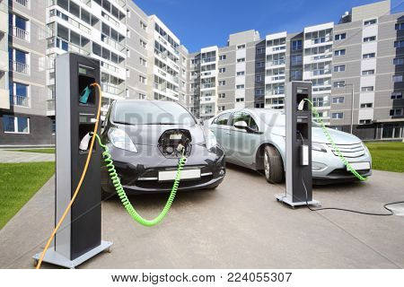 Two electric cars recharged at electrical charging in courtyard of multi-storey building, collage