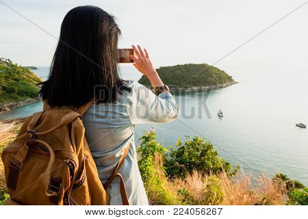 Asia Young traveler woman backpacker use mobile phone take a photo of beautiful of sunset nature at top of mountain sea view,Freedom wanderlust concept poster