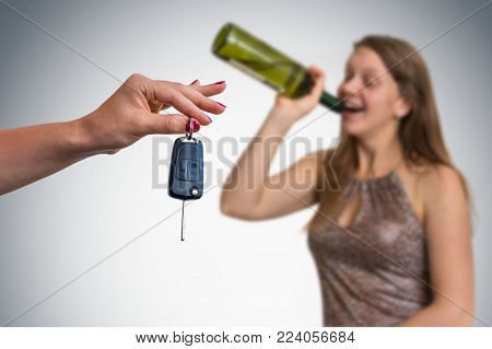 Unfocused woman drinking alcohol and her friend showing car keys - homecoming after party