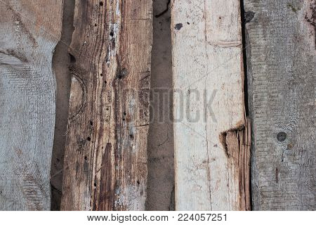 Weathered old wooden wall detail. Simple gray boards with knotholes and coarse grain nailed together. Outdoor. Backgrounds. Photo.