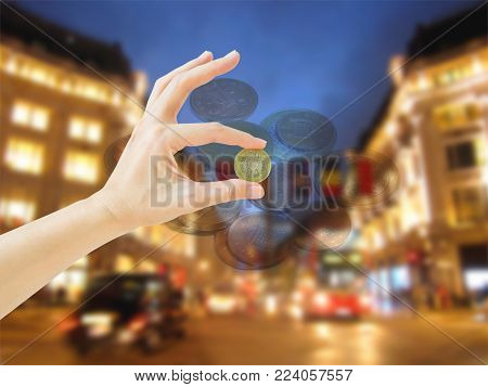 Hand holding two pounds british coin on Oxford Street at night background. Business and finance concept.