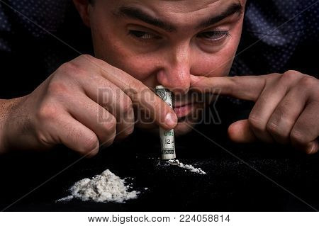 Junkie Man Snorting Cocaine Powder With Rolled Banknote