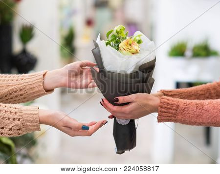 Safe and quick flower bouquet delivery for someone you love. Women hands holding a creative arrangement of roses dahlia and berries