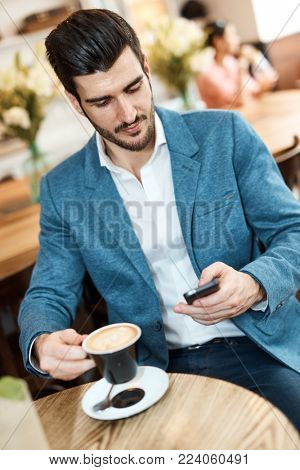 Young businessman sitting at cafe, using mobile, drinking cappuccino.