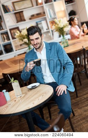 Young man enjoying cup of coffee at cafeteria, smiling.