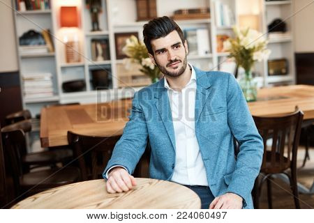 Young man sitting at table at cafeteria, looking away.