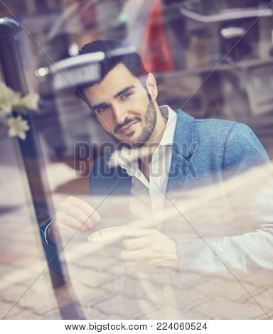 Handsome young man sitting at cafeteria, drinking coffee. Photographed through window from outside.